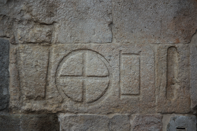 雕刻在PIAZZA ERBE墙上的过去的测量标志(不同的形状代表纺织品、餐饭、砖、谷物和种子)