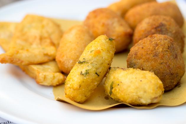 PANELLE(左侧——鹰嘴豆油煎饼,有时夹在三明治里食用)、CAZILLI DI PATATE(前面中间——油炸土豆丸子)、CROCCHE DI BECHAMEL(后面中间——贝夏梅尔酱炸丸子)、ARANCINI(右侧——大米丸子配肉酱或鸡内脏填馅)